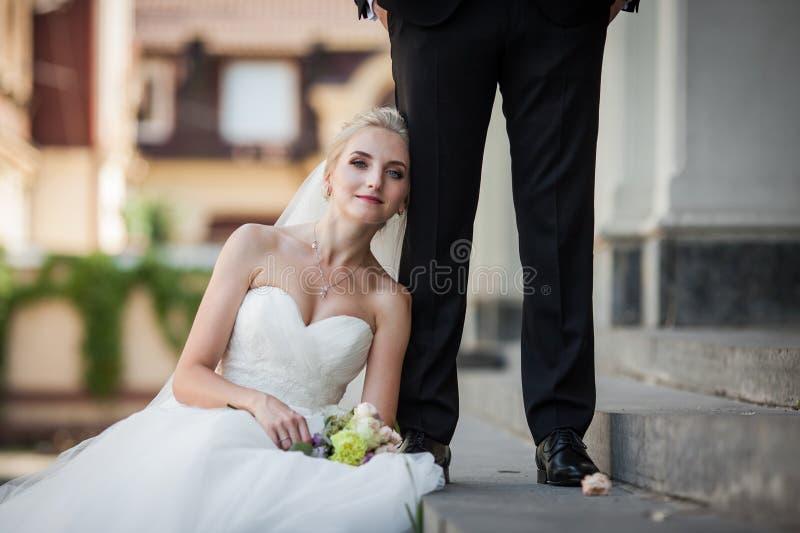 De mooie zitting van de blondebruid op treden, die tegen handso leunen royalty-vrije stock fotografie