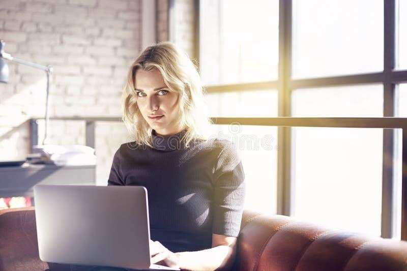 De mooie zitting van de blondeonderneemster in zonnig bureau die aan laptop werken Concept jongeren die mobiele apparaten werken royalty-vrije stock foto's