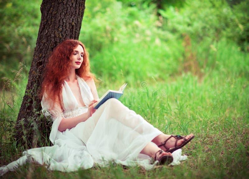 De mooie zitting van de gembervrouw onder boom en lezing een boek royalty-vrije stock foto's