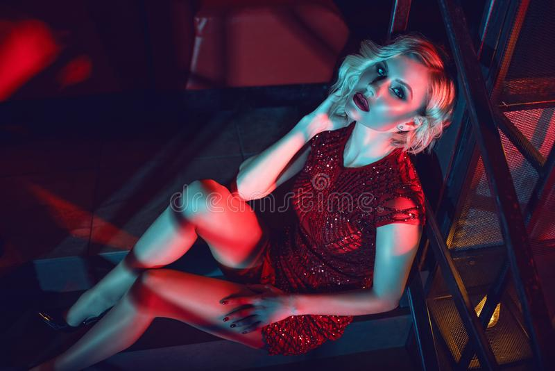 De mooie zitting van de glam blonde vrouw op de treden in de nachtclub in kleurrijke neonlichten stock foto's