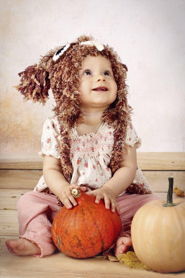 De mooie zitting van het babymeisje met pompoenen die gebreide hoed dragen royalty-vrije stock fotografie
