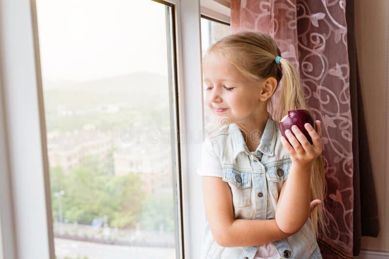 De mooie zitting van het blondemeisje op de vensterbank die thuis, in venster kijken en rode appel houden Gezond voedselconcept stock afbeeldingen