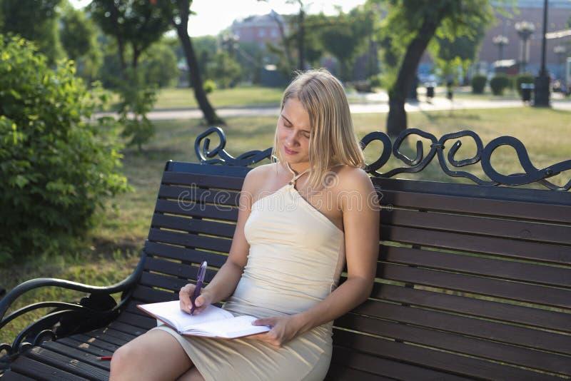 De mooie zitting van het blondemeisje in park die onderaan belangrijke nota's nemen royalty-vrije stock afbeelding