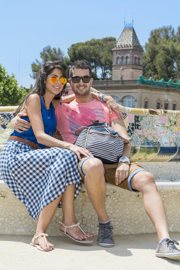 De mooie zitting van het liefdepaar op een bank in een Park Guel, Barcelona, Spanje stock afbeeldingen