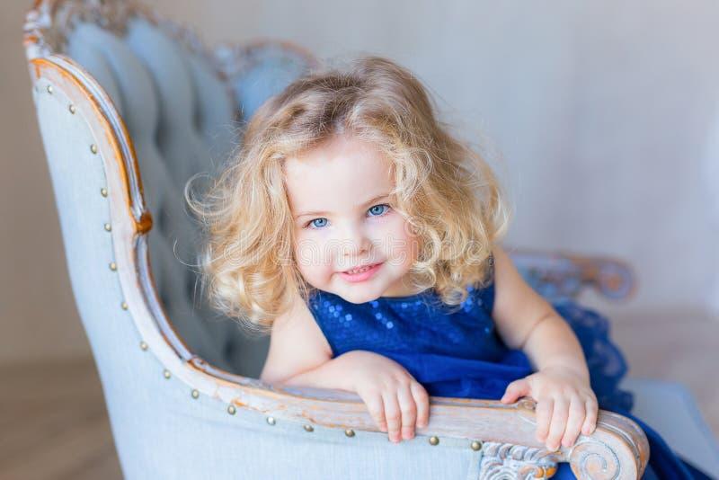 De mooie mooie zitting van het peutermeisje in leunstoel, het glimlachen stock afbeeldingen