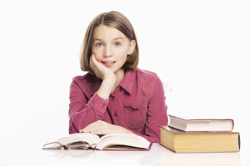 De mooie zitting van het tienermeisje bij een lijst met boeken royalty-vrije stock fotografie