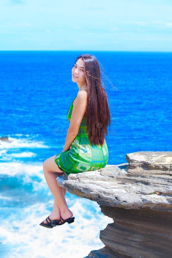 De mooie zitting van het tienermeisje op rotsachtige richel over blauwe oceaan royalty-vrije stock foto's