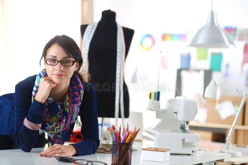 De mooie zitting van de manierontwerper bij het bureau in studio royalty-vrije stock afbeeldingen