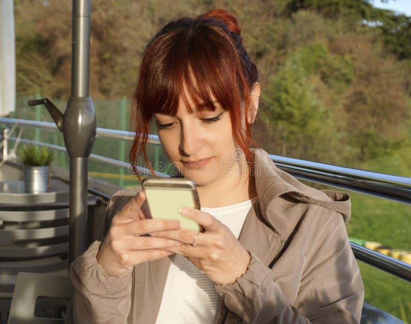 De mooie zitting van de roodharige jonge vrouw, het bekijken smartphone, het glimlachen en het schrijven SMS royalty-vrije stock fotografie