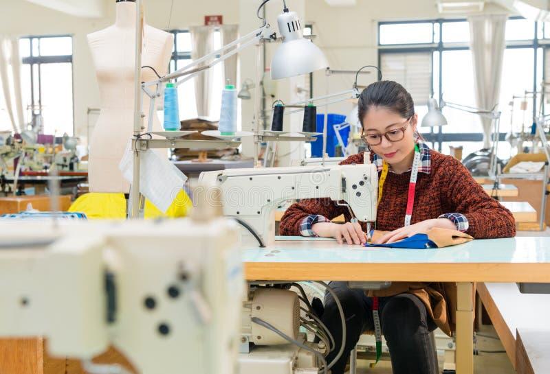 De mooie zoete naaiende vrouw van de kledingsfabriek stock foto