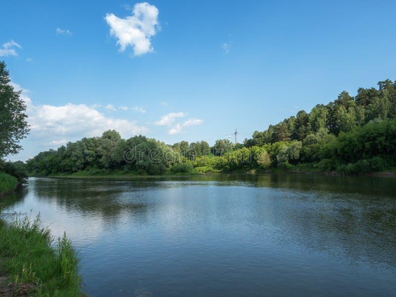 De mooie zomer peige De blauwe hemel wordt weerspiegeld in een diepe rivier op een heldere zonnige dag Wolk in de Hemel stock foto's