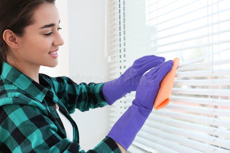 De mooie zonneblinden van het vrouwen schoonmakende venster met vod binnen stock foto's