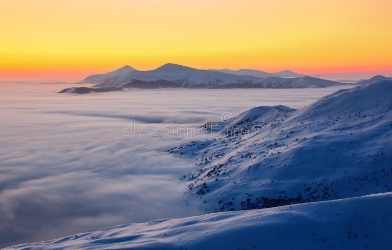 De mooie zonsondergang glanst informeert de schilderachtige landschappen met eerlijke die bomen met sneeuw en hooggebergte worden stock afbeeldingen