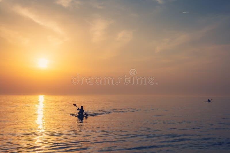 De mooie zonsopgang van de Zwarte Zee in Odessa met silhouet van het kayaking van de mens en warme kleuren royalty-vrije stock foto's