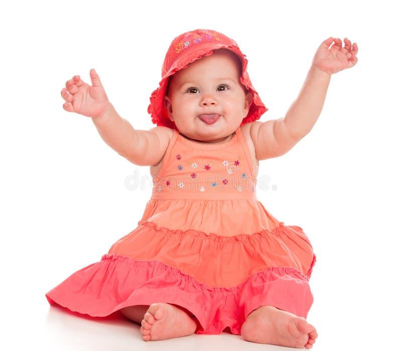 De mooie zuigeling zit in gebloeide kleding en hoed stock afbeelding