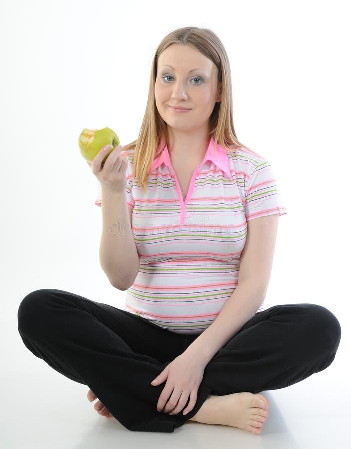 De mooie zwangere die appel van de vrouwenholding op een witte achtergrond wordt geïsoleerd royalty-vrije stock afbeeldingen