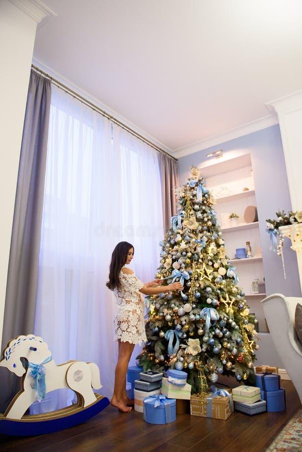 De mooie zwangere jonge vrouw verfraait een Kerstboom royalty-vrije stock afbeelding