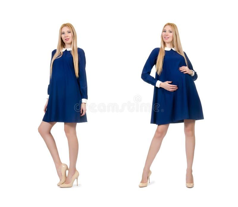 De mooie zwangere vrouw in blauwe die kleding op wit wordt ge?soleerd stock fotografie