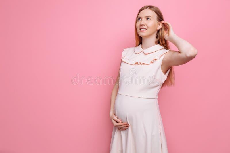 De mooie zwangere vrouw in een roze kleding, zet haar hand op haar buik op een roze achtergrond royalty-vrije stock afbeeldingen