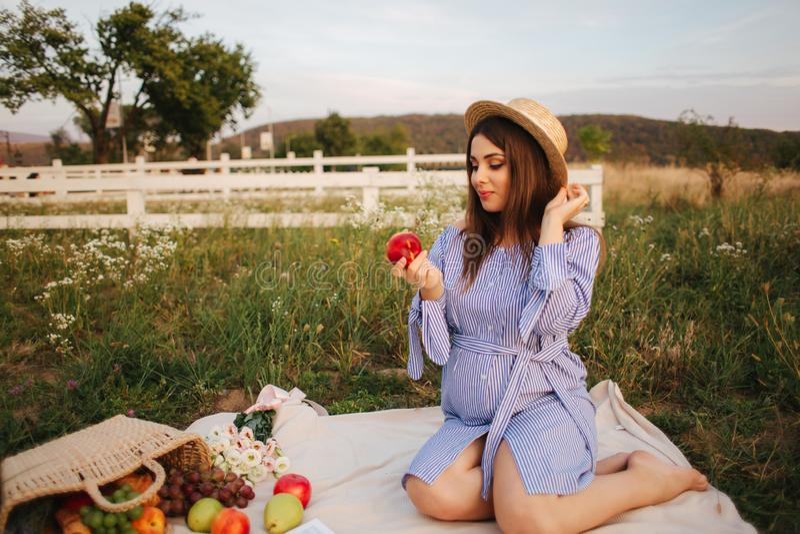 De mooie zwangere vrouw toont en eet rode appel Gezond voedsel Verse Vruchten Gelukkige vrouwenglimlach stock afbeeldingen