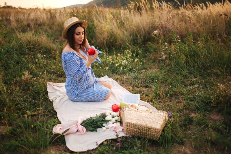 De mooie zwangere vrouw toont en eet rode appel Gezond voedsel Verse Vruchten Gelukkige vrouwenglimlach stock afbeelding