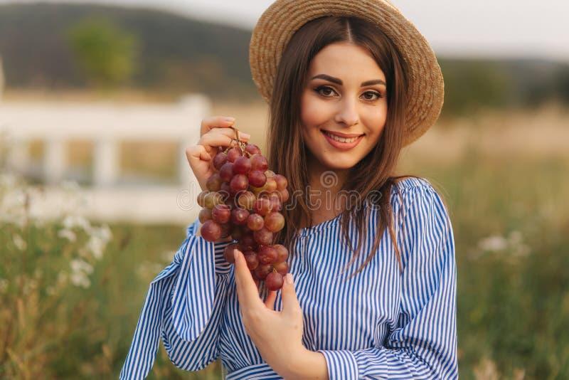 De mooie zwangere vrouw toont en eet rode druiven Gezond voedsel Verse Vruchten Gelukkige vrouwenglimlach royalty-vrije stock fotografie