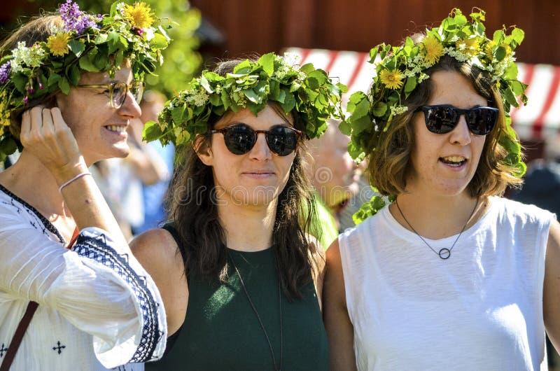 De mooie Zweedse zoete gelukkige vrouw geniet van traditionele decoratie die van medio de zomerdag kleurrijke verlofkroon in zonn stock foto