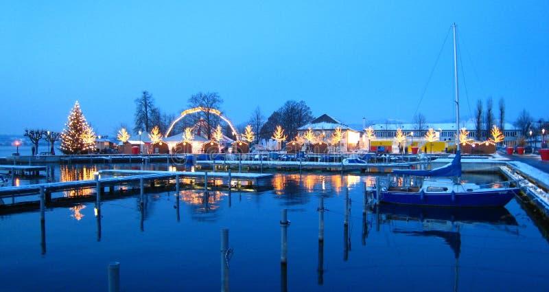 De mooie Zwitserse Kerstmismarkt in Zwitserland op de meerkust met sneeuw behandelde schepen bij het blauwe uur stock foto's