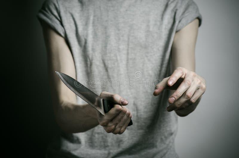 De moord en Halloween als thema hebben: een mens die een mes op een grijze achtergrond houden stock afbeeldingen