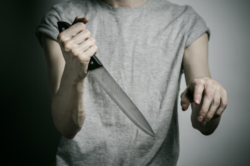 De moord en Halloween als thema hebben: een mens die een mes op een grijze achtergrond houden royalty-vrije stock foto