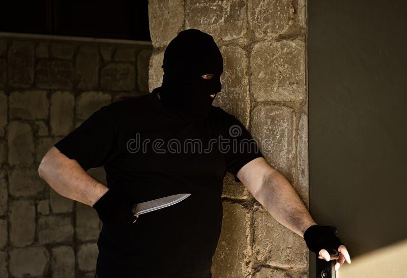 De moordenaar is bereid om in het huis te breken royalty-vrije stock foto