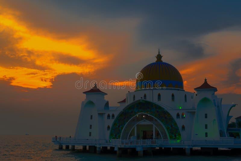 De Moskee van Melakadetroit bij zonsondergang door het water met oranje blauwe gr. stock afbeelding