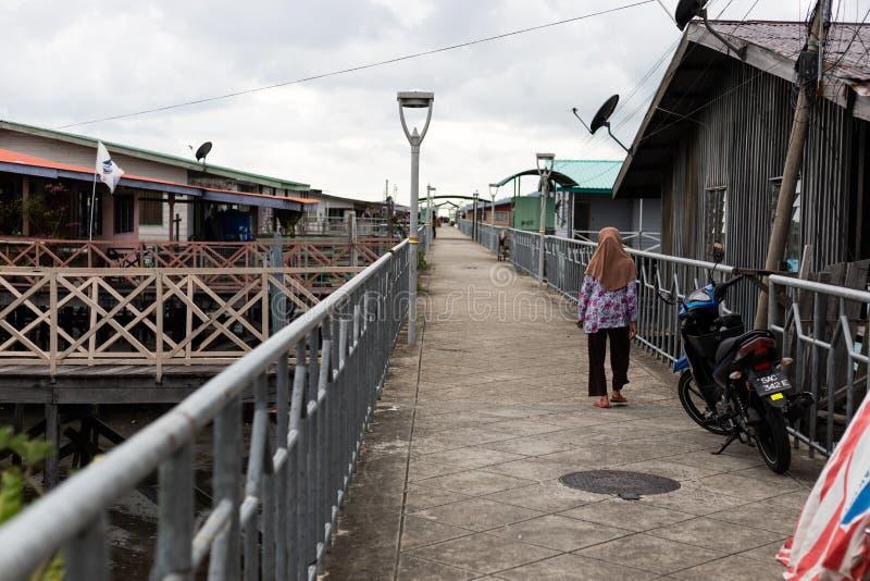 De moslim Aziatische Vrouw die van Islamhijab op Brugweg Residentia lopen stock afbeeldingen
