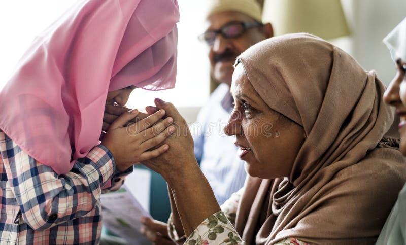 De moslimdochter kust haar moeder` s handen stock fotografie