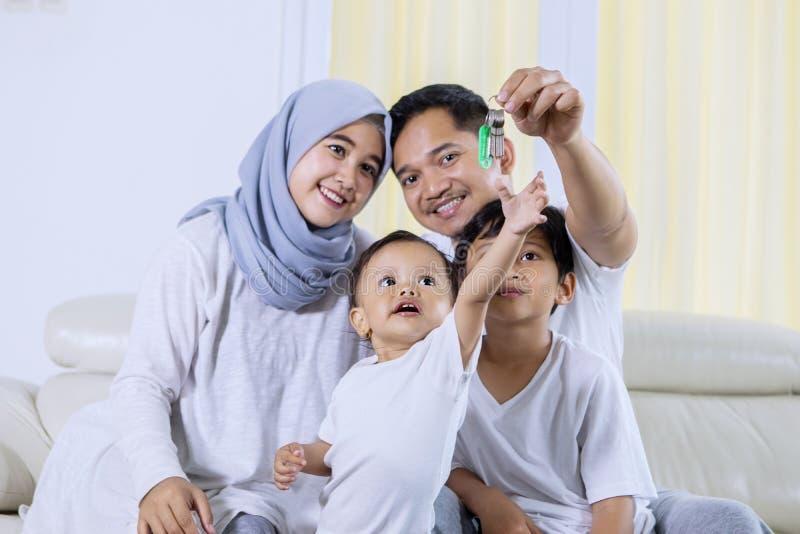 De moslimfamilie houdt sleutel aan hun nieuw huis stock foto