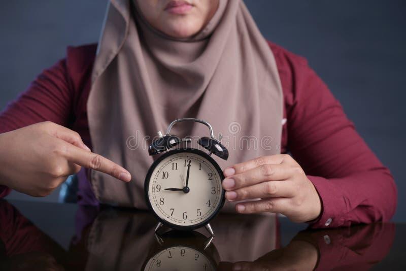 De moslimklok die van de Vrouwenholding op Negen O& x27 richten; Klok, Laattijdigheidsconcept stock foto's