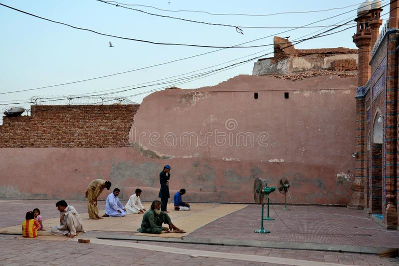 De moslimmensen bidden bij binnenplaats van het graf van het mausoleumheiligdom van Sufi heilige Sheikh Bahauddin Zakariya Multan royalty-vrije stock afbeelding