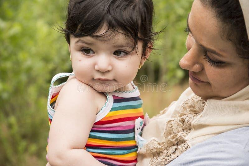 De moslimmoeder omhelste een kleine baby in openluchtenjo van het aardgebied royalty-vrije stock afbeeldingen