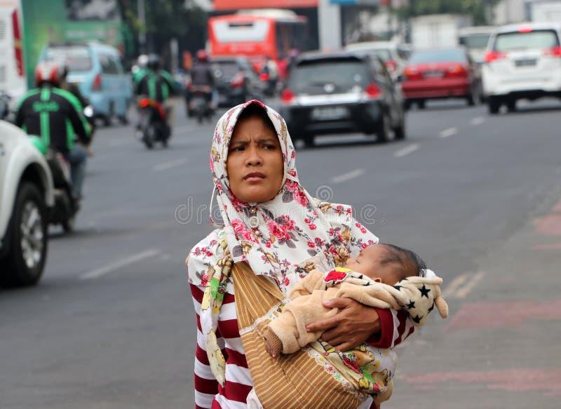 De moslimvrouw Indonesiër vervoert kinderen en het lopen op het voetpad naast de weg bij oude stadsbuurt in Djakarta stock afbeeldingen