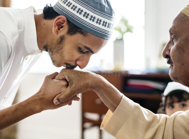 De moslimzoon kust zijn vader` s handen stock afbeeldingen