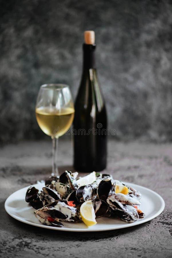 De mosselen kookten in een saus van witte die wijn, met toost en citroen wordt gediend stock fotografie