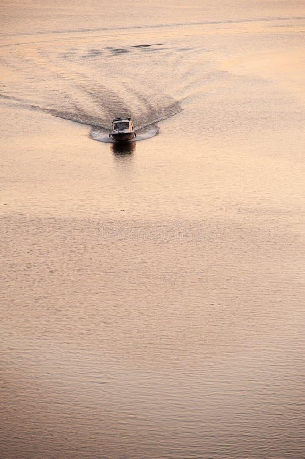 De motorboot drijft op een vlakke overzeese oppervlakte stock afbeeldingen