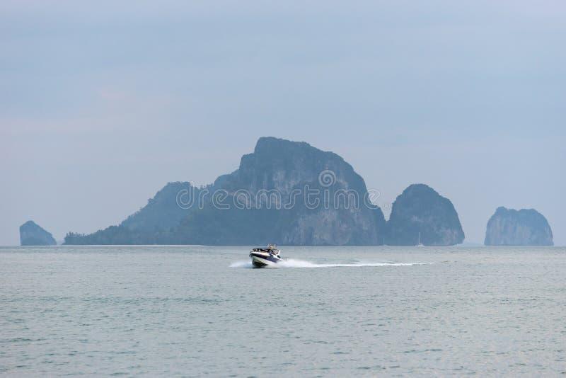 De motorboot in het zeewater tegen de grote klip op achtergrond keert terug terug royalty-vrije stock foto