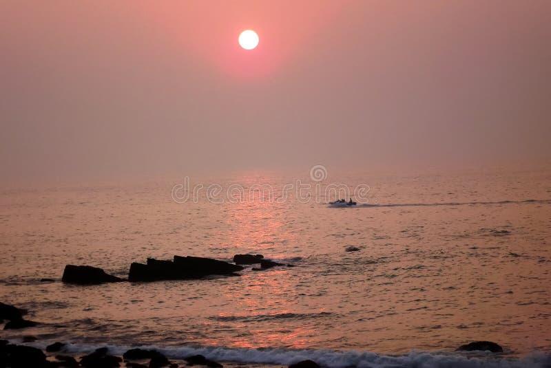 De motorboot kruist op overzees die op de trillende oranjegele kleur van de het plaatsen zon wijst royalty-vrije stock afbeelding