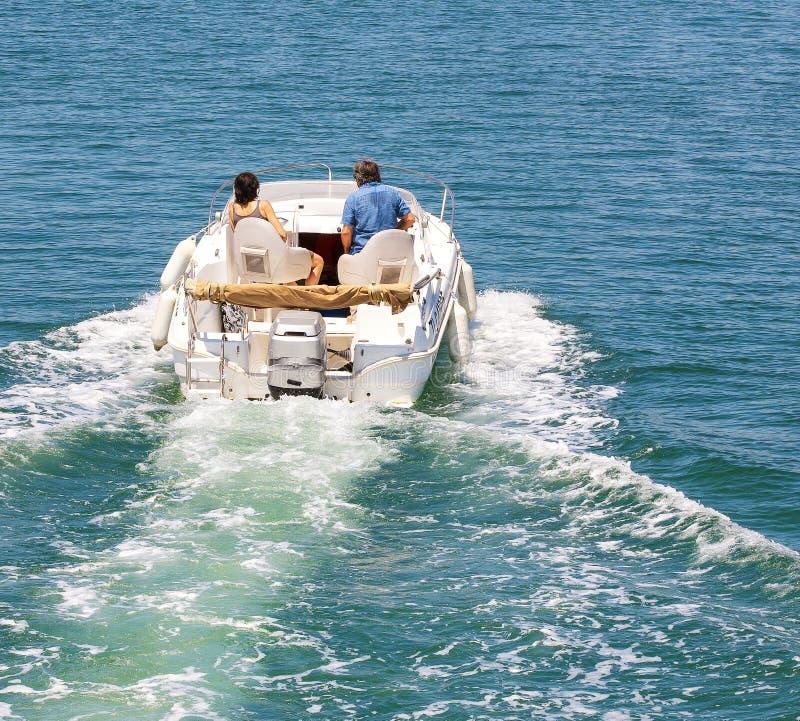 De motorboot met echtpaar bij in overzees landschap royalty-vrije stock foto's
