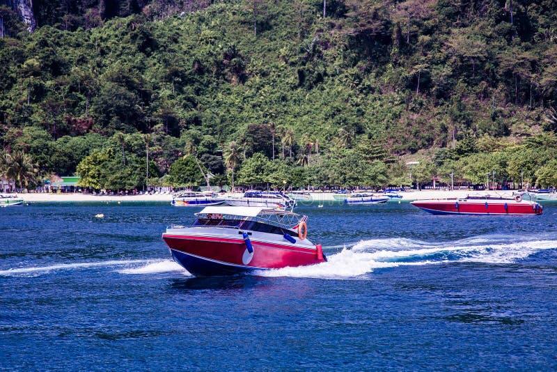 De motorboot versnelt Vlotters vanaf de kust, die achter hem grote golven verlaten stock afbeelding