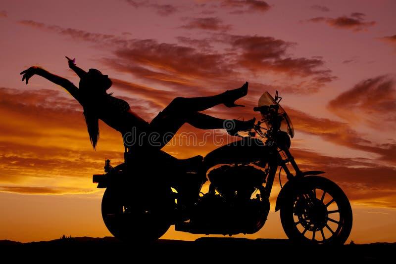 De motorfiets van de silhouetvrouw hielt omhoog handen achter stock foto's