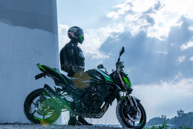 De motorrijder in een helm en in een beschermend kostuum bevindt zich onder de brug stock afbeeldingen