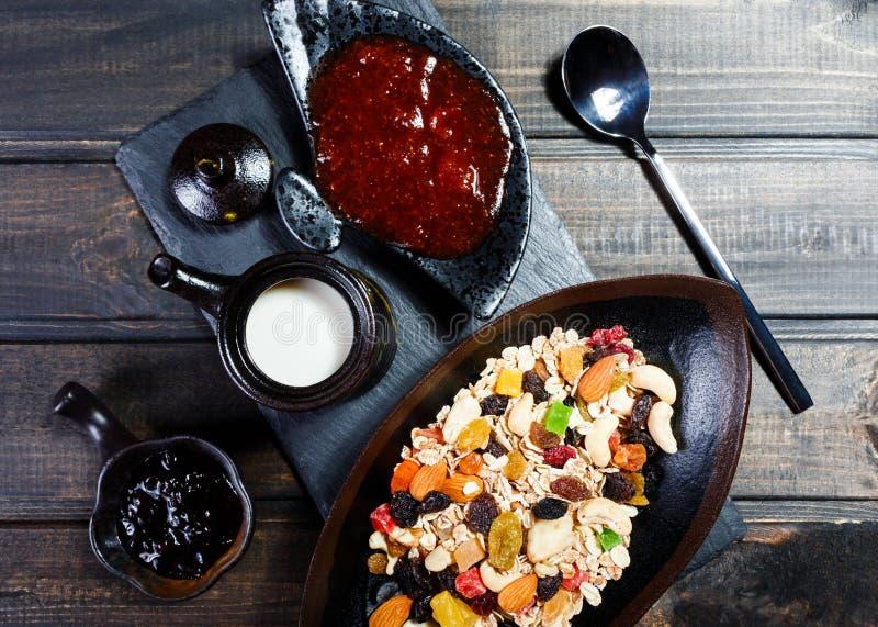 De Mueslikom met yoghurt, granola, sneed banaan, cachou, amandelen, Amerikaanse veenbessen, noten, droge vruchten mengeling op do stock afbeelding