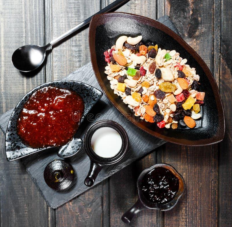 De Mueslikom met yoghurt, granola, sneed banaan, cachou, amandelen, Amerikaanse veenbessen, noten, droge vruchten mengeling op do royalty-vrije stock afbeeldingen